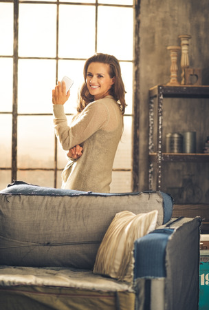 chic woman: Standing behind a sofa, looking over her shoulder, a brunette woman is holding her phone and smiling. Industrial chic ambiance and cozy atmosphere, sunlight is streaming through the loft window.
