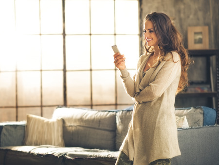 Seen in profile, a brunette woman in comfortable clothing is standing in a loft living room, looking down at her phone and smiling. Urban chic loft decoration details and window. Stockfoto