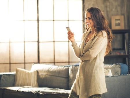 Von der Seite gesehen ist eine Frau, brünett in bequemer Kleidung, die in einer Loft-Wohnzimmer, schaut auf ihr Handy und lächelnd. Urbaner Chic Loft Dekoration Details und Fenster.