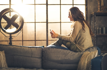 comfortable home: Seen from the side,a brunette woman is smiling, looking down at her phone sitting on the back of a sofa. Industrial chic ambiance and cozy atmosphere, sunlight is streaming through the loft window. Stock Photo