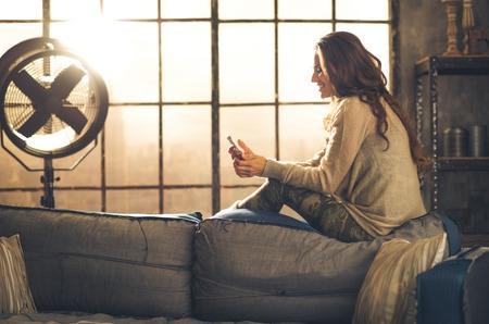 Visto desde el lado, una mujer morena está sonriendo, mirando a su teléfono que se sienta en la parte posterior de un sofá. Ambiente elegante Industrial y un ambiente acogedor, la luz del sol está fluyendo a través de la ventana del desván. Foto de archivo
