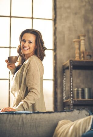 chic woman: A brunette woman in comfortable clothing is smiling over her shoulder, holding up a hot cup of coffee. Industrial chic background, and cozy atmosphere. Loft decoration details. Upper body shot.