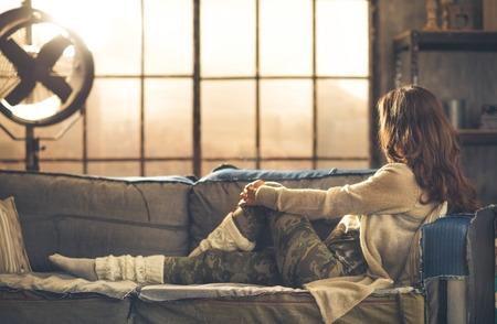 Von der Seite gesehen, Gesicht durch Haare verdeckt, eine Frau auf einem Sofa mit Blick über ein Loft-Fenster sitzen. Sonne scheint von der Industrie-Fan. Industrie-chic Ambiente und Stadtgefühl. Lizenzfreie Bilder