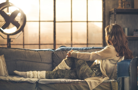 Seen from the side, face hidden by hair, a woman is sitting on a sofa looking out a loft window. Sun shines off the industrial fan. Industrial chic ambiance and urban feel.