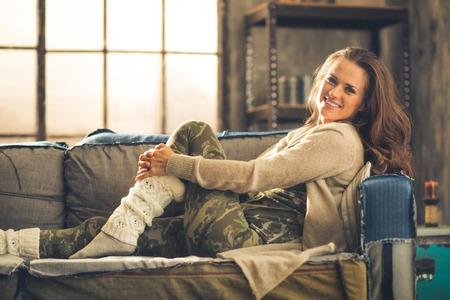 chic woman: An elegant brunette smiling woman in comfortable casual clothing, leggings, and a cardigan is relaxing on a loft sofa. Industrial chic ambiance and cozy atmosphere.