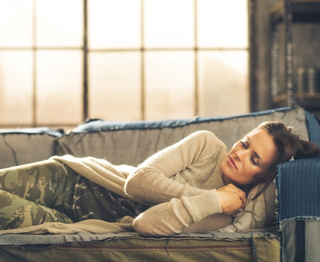 divan sofa: Cat-nap on a sofa. An elegant brunette woman napping on a sofa in a loft, curling her hands under her chin. Urban chic ambiance.