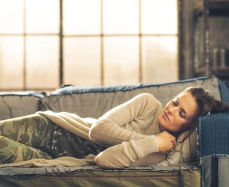 donne eleganti: Cat-pisolino su un divano. Un elegante donna bruna napping su un divano in un loft, arricciando le mani sotto il mento. Ambiente chic urbano.