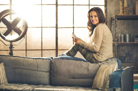 chic woman: A brunette woman sitting on a sofa back, she is looking over her shoulder and smiling. Wearing comfortable clothing, she is holding a tablet pc. Industrial chic ambiance and cozy atmosphere.