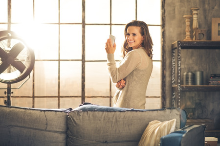 livingroom minimal: Standing behind a sofa, looking over her shoulder, a brunette woman is holding her phone and smiling. Industrial chic ambiance and cozy atmosphere, sunlight is streaming through the loft window.