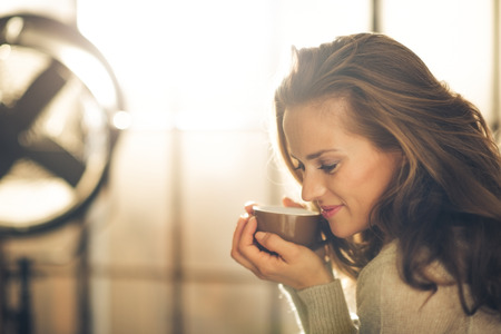 tea house: Close-up of a brunette woman in profile, head and shoulders only, holding and smelling a hot cup of coffee. Industrial chic background.