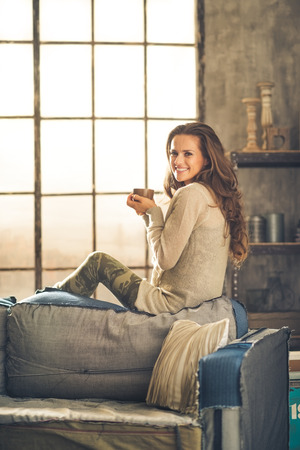 sofa: A brunette woman in comfortable clothing is is smiling and holding a hot cup of coffee, sitting on the back of a sofa. Industrial chic background, and cozy atmosphere. Loft decoration details.