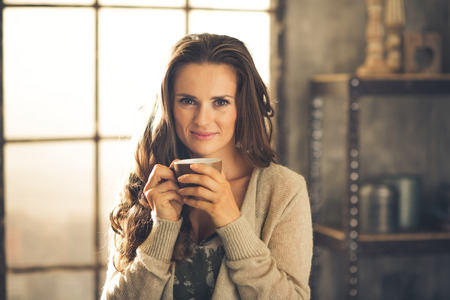 chic woman: Head and shoulder shot of a brunette woman in comfortable clothing is smiling gently over the top of her coffee cup. She is casually dressed and in a cozy loft atmosphere. Urban chic decoration. Stock Photo