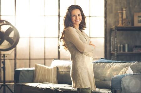 grunge cross: A smiling brunette woman in comfortable clothing is standing in a loft living room, arms crossed. Urban chic loft decoration details.