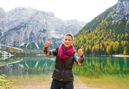 two thumbs up: A smiling and laughing brunette holding two thumbs up in approval while standing on the shores of Lake Bries. In the background, the still water reflects the autumn colours in the trees, and the Dolomite mountains. The great outdoors at their finest.