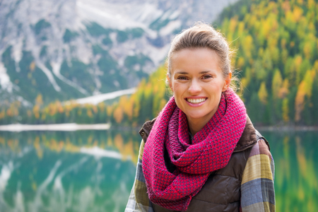 dolomite: Portrait of a smiling brunette. In the background, autumn colours and the Dolomite mountains are reflecting in the still water of Lake Bries. Fall colours and foliage. Stock Photo