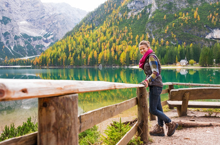 A smiling brunette hiker wearing outdoor gear stands facing the water and leaning against a wooden railing. The still water in the background provides a perfect mirror image of the mountains and trees. The autumn colours are golden.