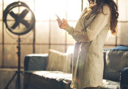 Close-up a brunette woman in comfortable clothing standing in a loft living room, holding her phone, arms crossed. Upper body shot, no face. Hair detail, and urban loft decoration. photo