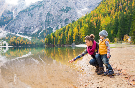 A mother, kneeling next to her daughter on the shores of Lake Bries, is pointing into the water. The colours of their hiking gear reflect the autumn foliage.