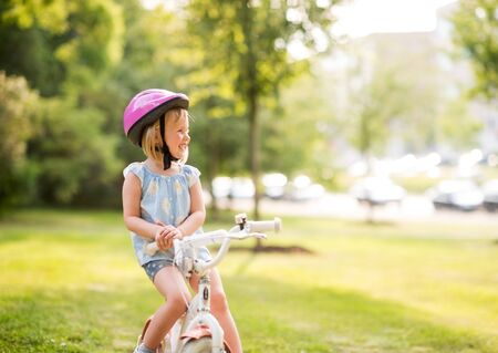 citypark: A young girl sits on her bicycle in a city park, smiling, resting, and happy. Wearing a pink helmet, she knows how to practice bicycle safety. The city park is vibrant green. Stock Photo