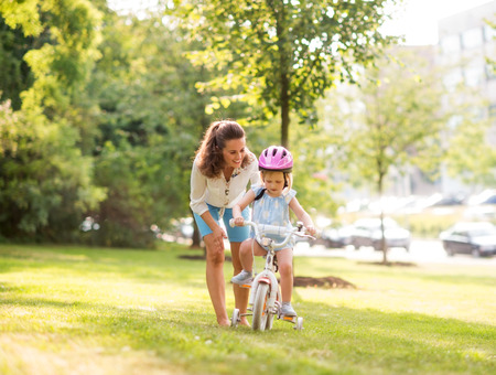 In a sunny city park, a mother gently pushes her blonde, blue-eyed daughter forward with encouragement as she learns to ride her bike. Thanks to her pink helmet, the daughter is practicing bike safety.