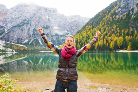 A happy, smiling woman hiker cheers for joy on the shores of Lake Bries. In the background, the still water reflects the fall colours in the trees, and the Dolomite mountains. The great outdoors. photo