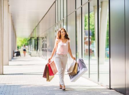 Een bruinharige vrouw met gedempte, zachte kleuren houdt vijf kleurrijke, patroon boodschappentassen loopt naar de deur van een exclusief winkelcentrum. Haar glimlach en houding laten zien een zelfverzekerde, sterke, gelukkige vrouw met de middelen om geld te besteden aan zichzelf. T
