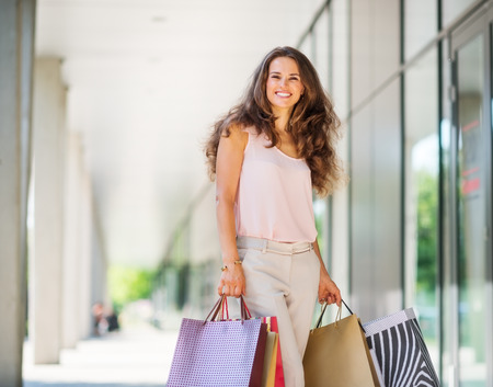 brown haired: A brown-haired woman wearing muted, gentle shades holds five colourful, patterned shopping bags during a successful shopping spree. Walking outside, she is enjoying the warmth of a summer day. Her smile is confident and happy. Shopping at exclusive shops, Stock Photo