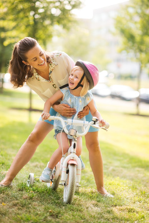 A mother hugs her daughter from behind, as the daughter wearing a pink helmet looks up towards her mother, laughing and proud. She has just learned to ride her bike by herself, and is proud of herself. Archivio Fotografico