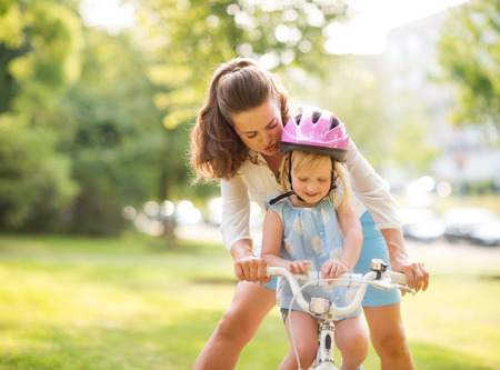 An encouraging mother helps her daughter learn how to steer her new bicycle. Wearing a pink helmet, the blonde daughter is proud and happy, looking down while smiling. The city park provides a warm, summery backdrop. Stock Photo