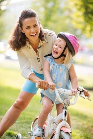 citypark: Giggles make the world go around! Summer time in the city park... A mother and daughter laugh together as the mother teachers her blonde, blue-eyed daughter how to ride her bike. Thanks to her pink helmet, the daughter is protected and safe.