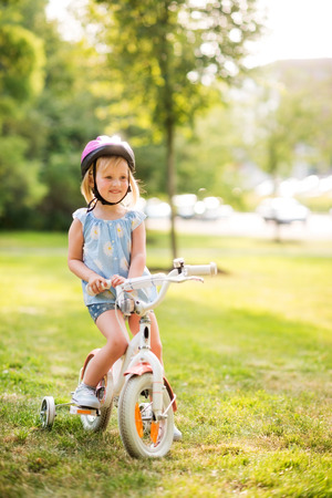 citypark: A young blonde, blue-eyed girl sits on her bicycle in a city park, smiling, resting, and happy. Wearing a pink helmet, she knows how to practice bicycle safety. The city park is vibrant green, and it is the summer time.
