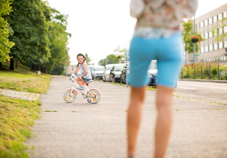 citypark: A young blonde, blue-eyed girl sits on her bicycle on a city sidewalk near a city park. The girl is smiling, happy, and looking back at her mother. Wearing a pink helmet, she knows how to practice bicycle safety. The perfect summertime activity...