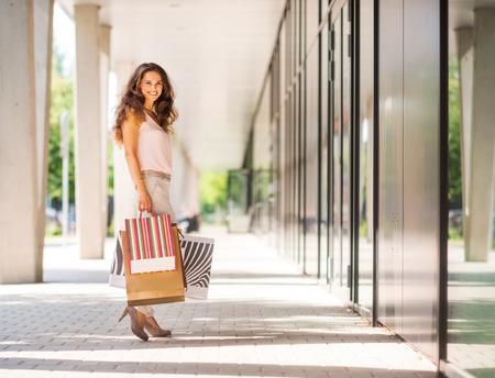 茶色の髪の女性が振り返る瞬間を停止、ビューアー。彼女は彼女の多くの購入について明確に幸せ、すべてはパターンでカラフルなショッピング バ
