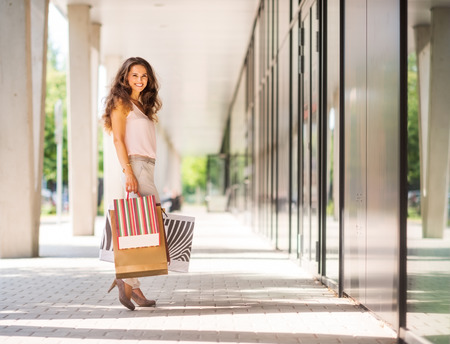 A brown-haired woman stops for a moment to look back a the viewer. She is clearly happy about her many purchases, all held in colourful shopping bags with patterns that contrast with the muted, gentle background colours. The doors lead into an exclusive s