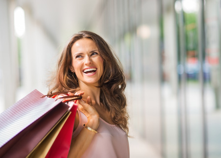 shopping spree: A brown-haired woman holding three shopping bags - brown, gold, and red - over her right shoulder looks back at someone who is making her laugh. A good shopping spree makes any woman happy. She is content, exudes elegance and effortless style. She looks a Stock Photo