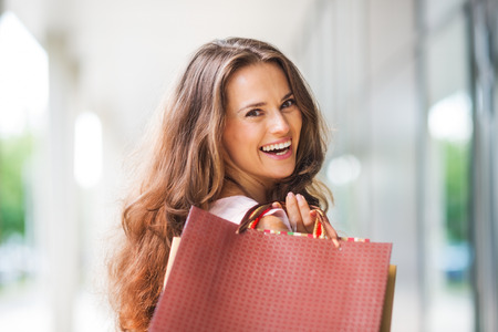 effortless: A brown-haired woman holding shopping bags - with a brown, textured bag most prominent - over her right shoulder looks back at the viewer in total happiness. She is content, care-free, has a gorgeous smile, and is elegant. Her style is effortless and clas