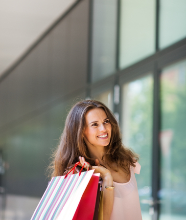 approachable: A brown-haired woman holding three colourful shopping bags over her shoulders smiles gently. She is relaxed, content, care-free, and elegant. Her style is effortless and classic. Her wide smile make her approachable, happy, and warm. The sunlight plays on Stock Photo