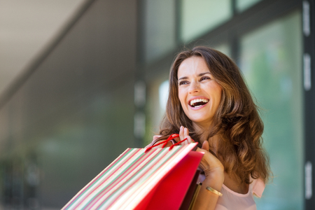 approachable: A brown-haired woman holding a striped, multi-coloured shopping bag over her right shoulder laughs and smiles while looking backwards. She is relaxed, happy, and effortlessly stylish and classic. Her wide smile make her approachable, happy, and warm. The  Stock Photo