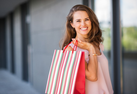 A brown-haired woman is seen from the waist up. She holds a striped, multi-coloured and red shopping bag over her right shoulder. Her smile is relaxed and happy. She is effortlessly stylish and classic. Her wide smile make her approachable, happy, and war