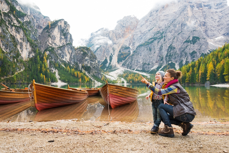 A smiling brunette mother kneels next to her daughter, pointing up. In the background, wooden boats float on the water, autumn colours, the Dolomite mountains, and forest.