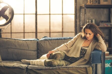 chic woman: An elegant brunette woman wearing comfortable, casual clothing, leggings, and a cardigan is relaxing on a sofa in a loft. Sunlight shines through the window. Cozy atmosphere, industrial chic.