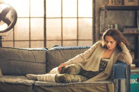 Een elegante brunette vrouw dragen van comfortabele, casual kleding, leggings, en een vest is ontspannen op een bank in een loft. Zon schijnt door het raam. Gezellige sfeer, industriële chic.