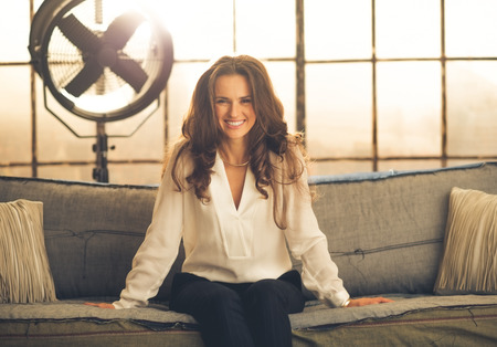 leaning forward: An elegant brunette is sitting a sofa in a loft, leaning forward and smiling. In the background, light is shining through a large window, industrial fan. Industry chic.