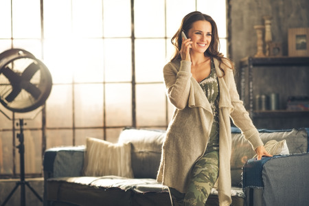 Seen from the front, a brunette woman in comfortable clothing is standing in a loft living room, leaning against the sofa, talking on her phone and smiling. Urban chic loft decoration details. Stock Photo