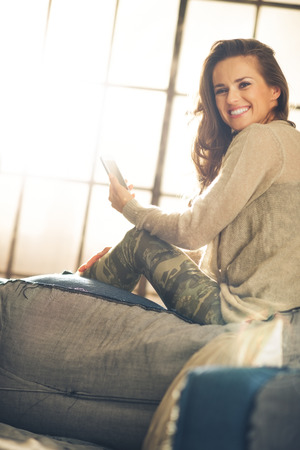 chic woman: Looking over her shoulder, a brunette woman is holding her phone and smiling. Industrial chic ambiance and cozy atmosphere, sunlight is streaming through the loft window.