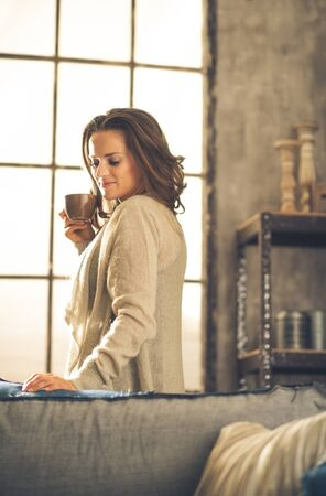 chic woman: A brunette woman in comfortable clothing is is smiling and holding a hot cup of coffee, looking down. Industrial chic background, and cozy atmosphere. Loft decoration details. Upper body shot.