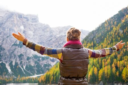 Seen from behind, a woman brunette hiker holds her arms wide open in joy. In the background, autumn leaves and the Dolomite mountains. photo