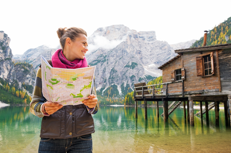 An smiling brunette wearing outdoor gear is looking sideways, holding an open map in her hands. Behind her, the Italian Dolomites are reflected in the still water. The water provides a mirror reflection of the autumn leaves and colours, and the rustic woo photo