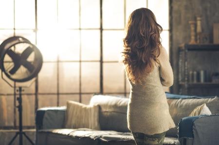 Van achteren gezien, is een donkerbruine vrouw in comfortabele kleding staande in een loft woonkamer, kijkt uit het raam loft. Urban chic loft decoratie details.