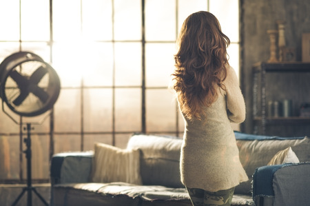 Seen from behind, a brunette woman in comfortable clothing is standing in a loft living room, looking out the loft window. Urban chic loft decoration details.